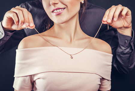 Man helping his girlfriend to try on a golden necklace on black background. Gift for Valentines day.