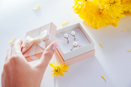Woman opens a gift box with a set of pearl jewellery surrounded with flowers