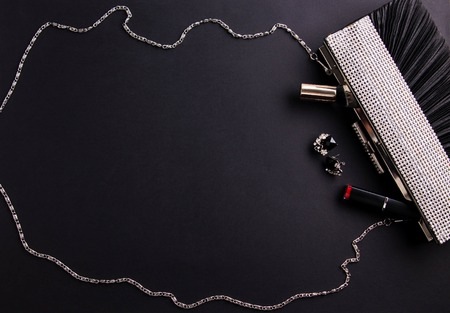 Contents of female handbag including jewellery and cosmetics on black background