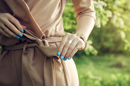 Woman with blue manicure wearing stylish outfit with accessories outside Stock Photo