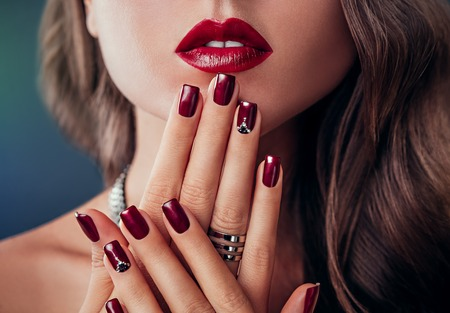 Beautiful woman with red lips and burgundy manicure Фото со стока