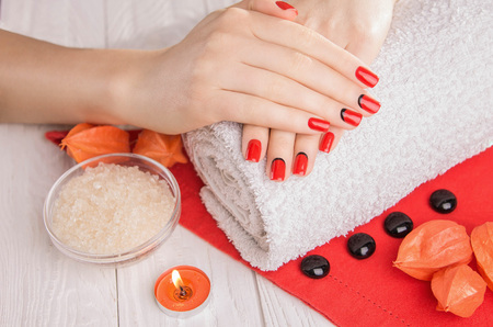 Red manicure with dekor and towel on white wooden table. Spa essentials.