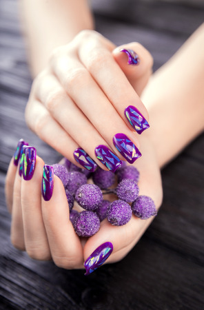 Shattered glass purple manicure on black wooden background