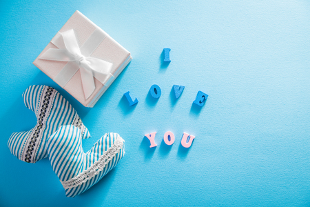 Gift box with I love you lettering and hearts on blue background. Valentines day concept.