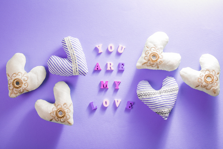 Hearts with romantic lettering on purple paper background. Valentines day concept.