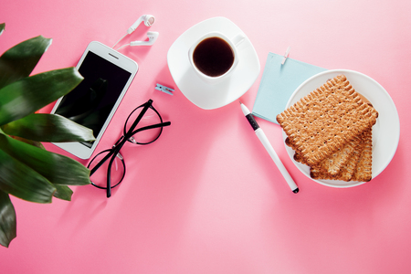 Coffe break of an office employee. Working with a cup of coffee and snacks, using a smartphone