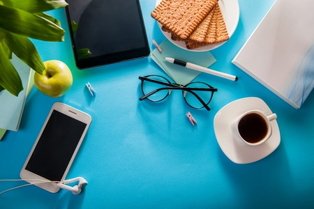 Workspace of a student on blue background. Studying with a cup of coffee and snacks, using a phone Standard-Bild