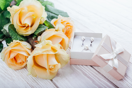 Pearl earrings in the gift box with roses on wooden background Stock Photo