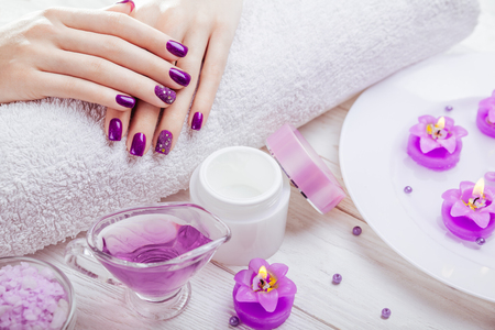 Beautiful purple manicure with spa essentials on wooden background