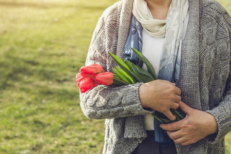 Woman holds a bouquet of red tulips