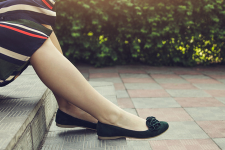 Young woman wearing green suede flats outside