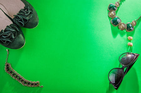 Green flats and accessories on green background Stock Photo