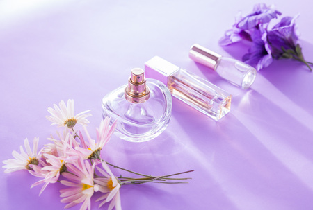 Bottles of perfume with flowers on purple background