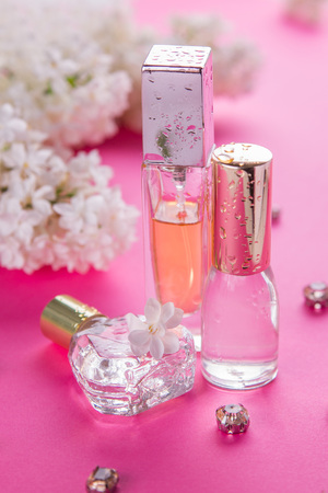Bottles of perfume with white lilac on pink background Imagens