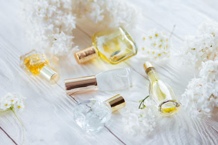 Bottles of perfume with white flowers on wooden background