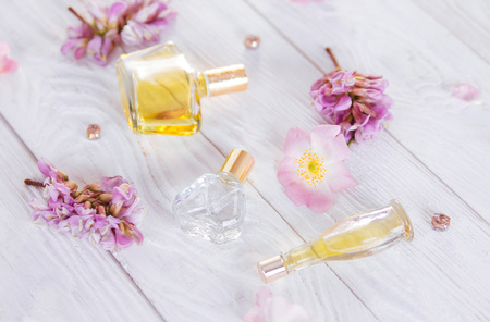Bottles of perfume with flowers on white background Stock Photo