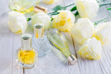 Bottles of perfume with eustoma flowers on white background