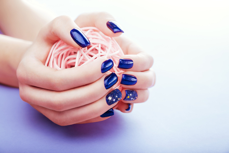 Woman with blue manicure holds a ball on blue background