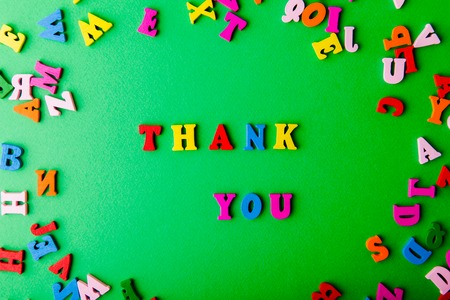 Thank you. Scattered colorful wooden letters on green background Stock Photo