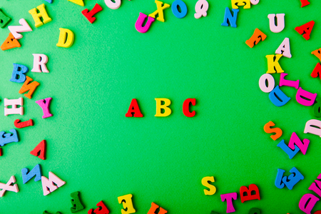 English ABC. Scattered colorful wooden letters on green background Stock Photo