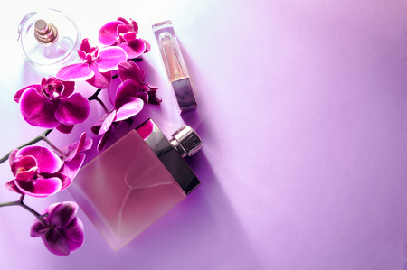 Bottles of perfume with violet orchid on purple background Stock Photo