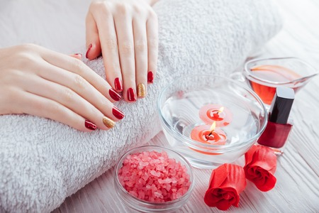Red and golden manicure design with spa essentials on white wooden table. Skin treatment Stock Photo