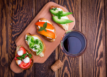 Brushetta set for wine. Variety of small sandwiches on wooden background