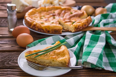 Cabbage pie with onion on wooden table