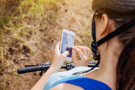 Young bicyclist searching for the right way using a navigator on her phone