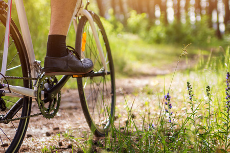 Young bicyclist riding in the forest in the morning