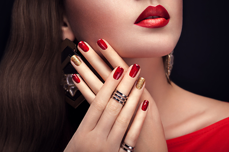 Beautiful woman with perfect make-up and red and golden manicure wearing jewellery on black background