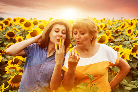 Middle-aged mother and her daughter having fun in sunflower field at sunset. Doing manicure made of sunflower petals