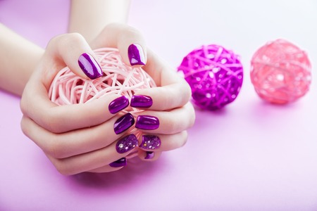 Woman with purple manicure holds a ball on pink background