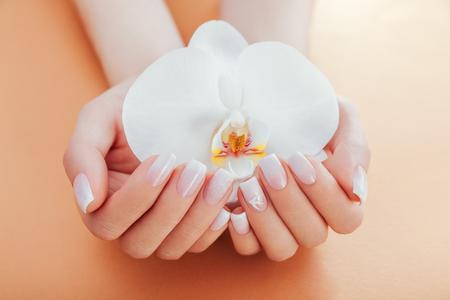 Ombre manicura francesa con destellos y orquídeas sobre fondo naranja. Mujer con manicura francesa ombre blanco tiene flor de orquídea. Cuidado del cuerpo
