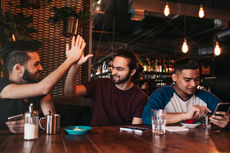 Happy arabian young man giving high five to his friend. Group of mixed race people having fun in lounge bar. Friends hangout and laughing