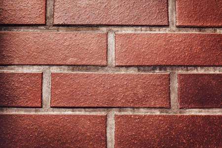 Red brick wall background. Texture of a stone wall. Close-up of bricks. Space