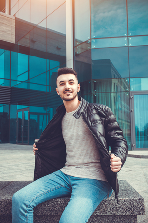 Arabian man taking his coat off in front of modern building. Young man shows off. Guy chilling out Stock Photo
