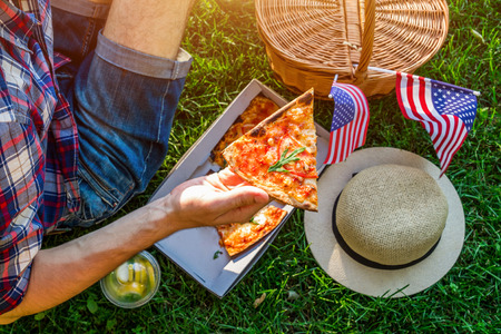 Young man celebrating Independence Day of America in the park. Man and woman having pizza with lemonade. Picknick basket with USA flag. Stockfoto
