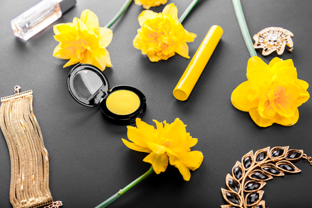 Beautiful jewellery and cosmetics with yellow flowers. Jewelry, accessories and organic cosmetics on black background Banque d'images