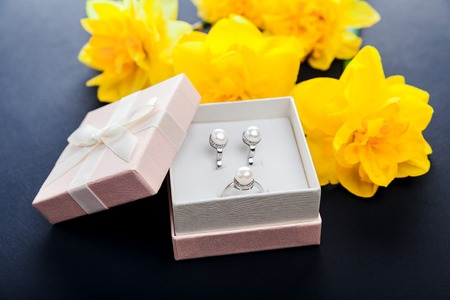Set of pearl jewellery in gift box with flowers on black background. Silver earrings and ring with pearls as a present for Mothers day. Accessories and jewelry.