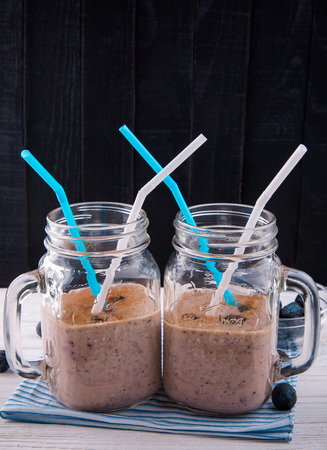 blueberry smoothie in the glass jars on black wooden background. Healthy eating. Healthy diet