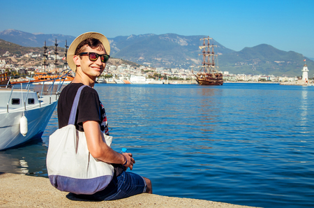Young happy man looks at the Alanya port surrounded by mountains. Smiling traveller sitting by the sea. Vacation concept