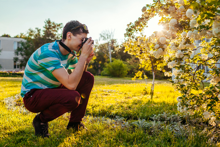 Man photographer taking pictures of flowers in park at sunset. Young guy enjoys his hobby using a camera outside.