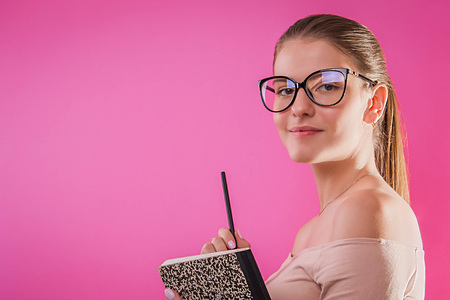 Portrait of a pretty student with a copybook wearing glasses on pink background. Young girl studying
