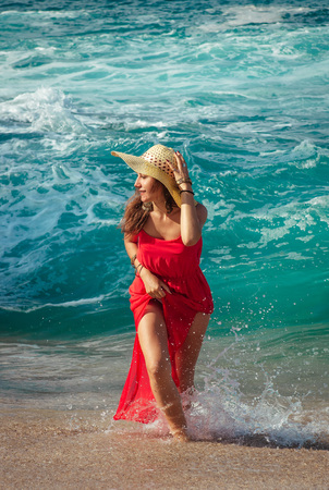 Beautiful woman in red dress runs away from waves on the beach
