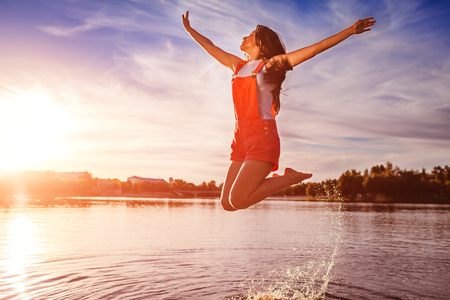 Happy and free young woman jumping and raising arms on river bank. Freedom. Active lifestyle. Summer holidays
