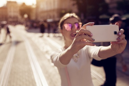 Happy young woman tourist takes selfie in old city using smartphone. Summer travel. Vacation and holidays concept