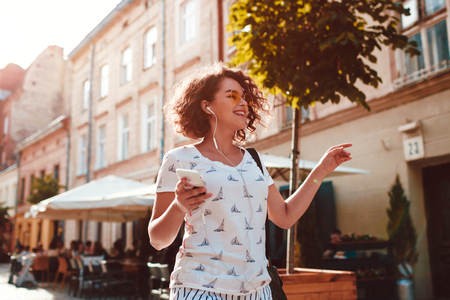 Beautiful teen girl listening to the music walking along old city streets and dancing Happy woman having fun