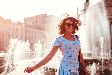 Happy young woman with backpack walking by fountain in summer. College girl chilling outdoors after classes