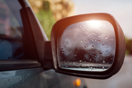 Side rear-view mirror on a modern car. Rainy water drops on glass. Sun reflection.